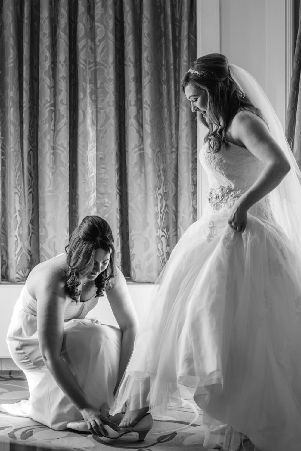 bridesmaid putting bride's shoes on