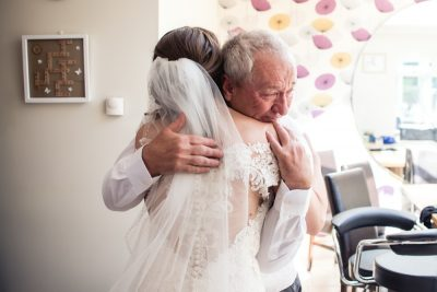 father of the bride hugging daughter
