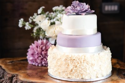 lilac purple and white wedding cake with ruffles and flowers
