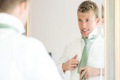 groom adjusting tie reading wedding