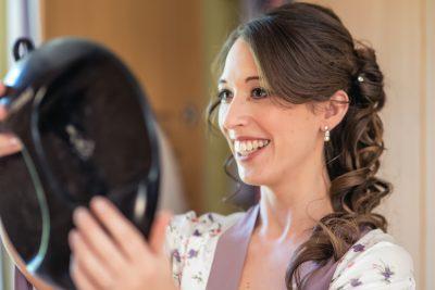 bride checking makeup during bridal prep