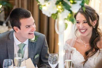 bride and groom laughing at speeches rustic wedding venue